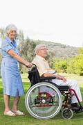 Elderly woman pushing partner in wheelchair through the park - stock photo