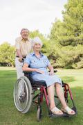 Man pushing partner in wheelchair through the park - stock photo