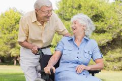 Elderly man laughing with his partner in a wheelchair - stock photo