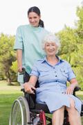 Portrait of nurse pushing elderly woman in wheelchair Stock Photos