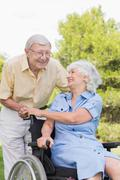 Stock Photo of Older man laughing with his partner in a wheelchair