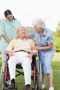 Man in wheelchair chatting with his nurse and partner - stock photo