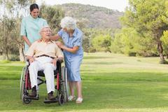 Elderly man in wheelchair chatting with his nurse and partner - stock photo
