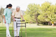 Elderly man walking in park with zimmer frame - stock photo