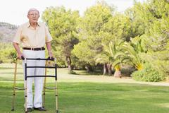 Portrait of old man using zimmer frame Stock Photos