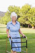 Elderly woman using a zimmer frame to walk - stock photo
