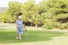 Elderly woman walking with a zimmer frame - stock photo