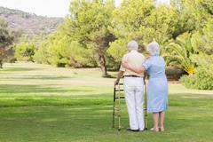 Elderly couple standing in the park Stock Photos
