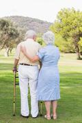 Elderly couple standing in a park - stock photo