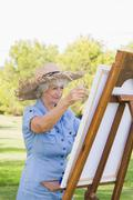 Stock Photo of Woman wearing straw hat painting in the park