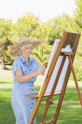 Old woman painting on an easel in the park - stock photo