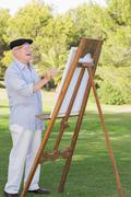 Old man painting outside - stock photo