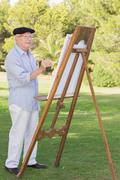 Old man painting outside using an easel - stock photo