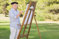 Portrait of man painting in the park - stock photo