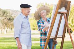 Elderly couple painting in the park - stock photo