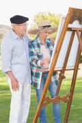 Old couple painting in the park - stock photo