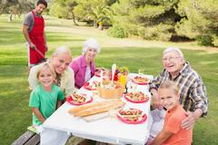 Portrait of happy family at picnic table - stock photo