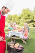 Father cooking barbecue for family - stock photo