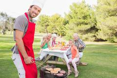 Smiling father cooking barbecue for family - stock photo