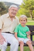 Portrait of grandfather and grandson in the park - stock photo