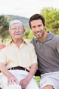 Portrait of father and adult son smiling - stock photo