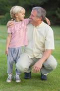 Grandfather crouching beside grandson looking at each other - stock photo