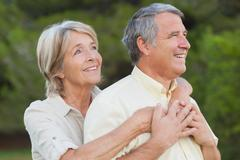 Stock Photo of Older couple looking away and embracing