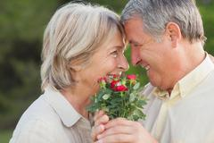 Older couple looking at each other and holding flowers - stock photo