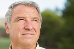 Thoughtful grey haired man looking into distance - stock photo