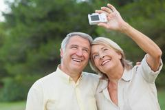 Stock Photo of Older couple taking a photo of themselves and smiling