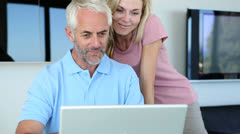 Man using his laptop with his wife - stock footage
