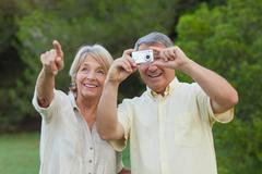 Couple taking a photo of something in the park Stock Photos