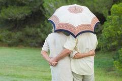 Couple embracing under a parasol - stock photo