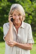 Portrait of older woman on her phone - stock photo