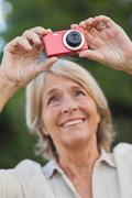 Older blonde woman taking a photo - stock photo