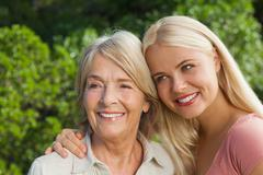 Smiling mother with adult daughter posing - stock photo