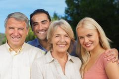 Parents posing with adult offspring and partner - stock photo
