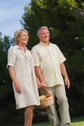 Older couple walking with basket of fruit Stock Photos