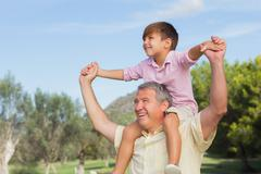 Stock Photo of Happy grandfather giving cute grandson a piggy back and having fun
