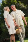 Stock Photo of Happy older couple walking with basket of fruit