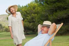 Older man relaxing in deck chair with his partner approaching - stock photo
