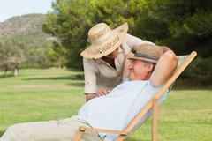 Older man relaxing in deck chair with his partner saying hello - stock photo