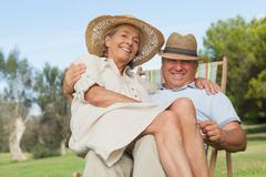 Woman sitting on lap of partner sitting in deck chair - stock photo