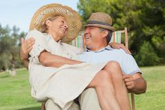 Woman sitting on lap of partner sitting in deck chair and smiling at him - stock photo