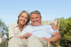 Portrait of older couple with man sitting in deck chair - stock photo