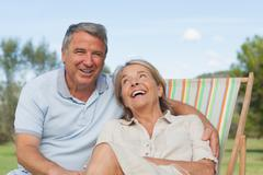 Couple laughing together with woman sitting in deck chair Stock Photos
