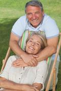 Portrait of older couple with woman in deck chair - stock photo