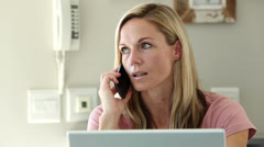 Frustrated woman shaking her head while she is on the phone Stock Footage