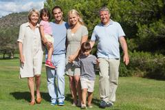 Multi-generation family portrait strolling through the park - stock photo