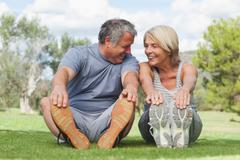 Happy older couple stretching in the park - stock photo